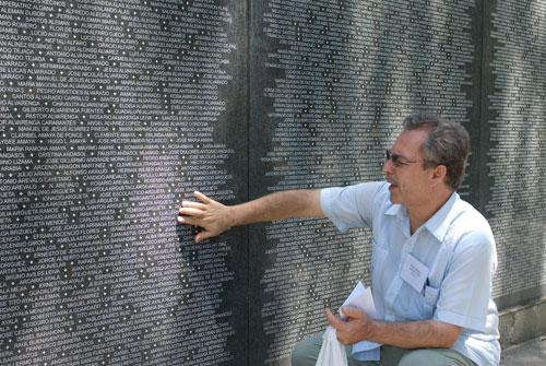 Jose pointing at the memorial wall where his name could have been.